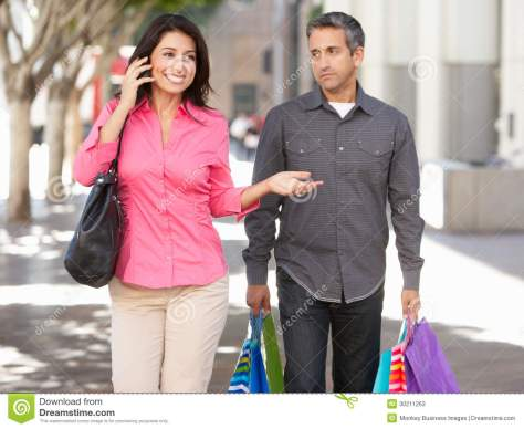 fed-up-man-carrying-partners-shopping-bags-city-street-walking-30211263